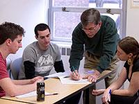 Students and faculty gather around a conference table
