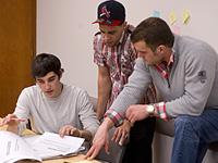 Three students gather around a table and review papers